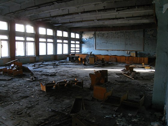 A large classroom, empty except for old desks and chairs, or what's left of them.