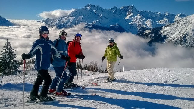 Four skiers standing in front of a mountain panorama