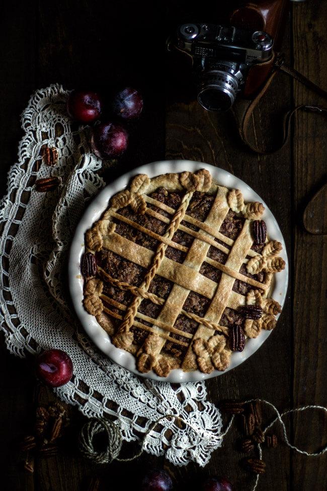 Pflaumen Pekannuss Pie goldbraun im Ofen gebacken mit herbstlicher Verzierung. Teigzöpfe, Teigblätter machen die Pie Kruste aufwendig