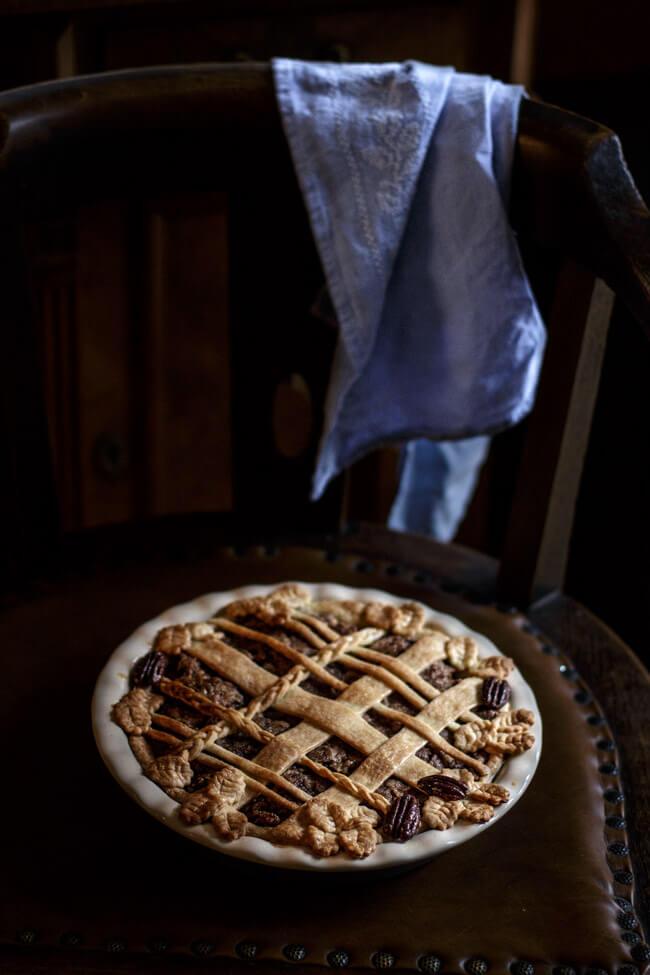 Pflaumen Pekannuss Pie mit aufwendiger Verzierung auf antikem Stuhl mit Lederpolster und blauem Geschirrtuch