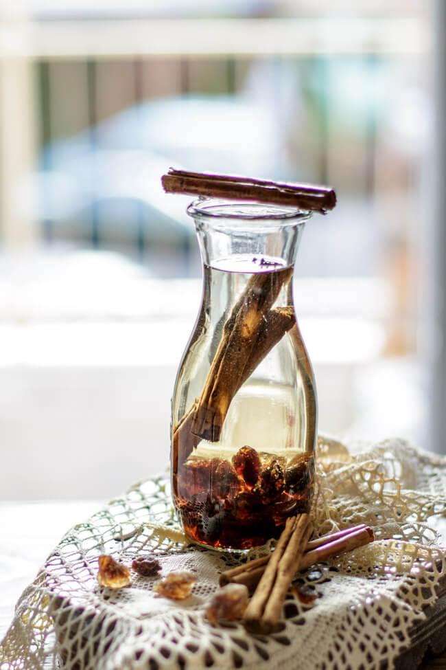 WEckflasche mit zwei Zimtstangen und braunem Krustnkandis ergibt Zimt Likör.