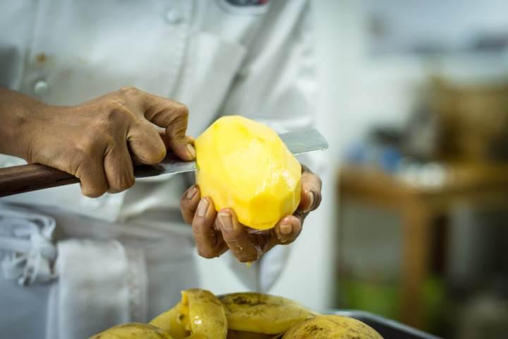 Thailänderin schneidet gelbe Thai Mango