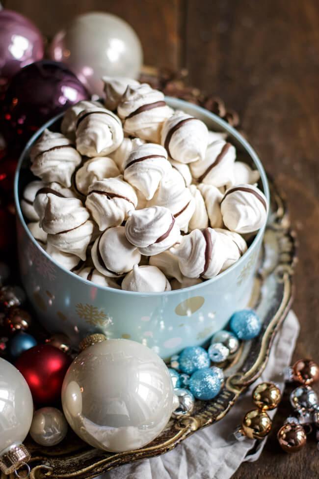 Feenküsschen - Baiser mit Schokolade in blauer Keksdose auf Weihnachtsteller mit Christbaumkugeln