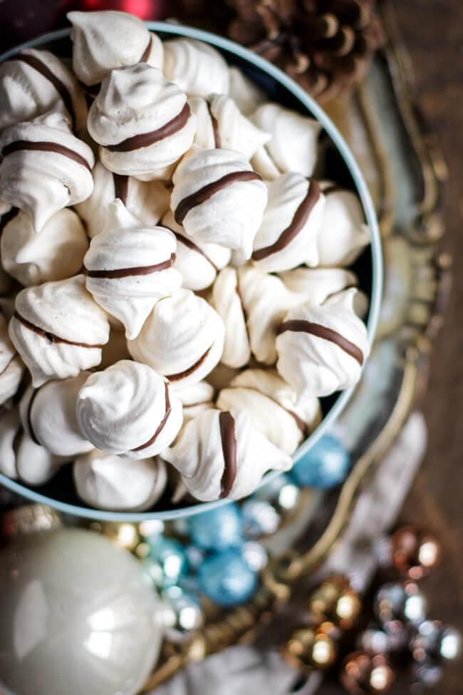 Feenküsschen - Baiser mit Schokolade in blauer Keksdose auf Weihnachtsteller mit Christbaumkugeln - Ansicht von oben
