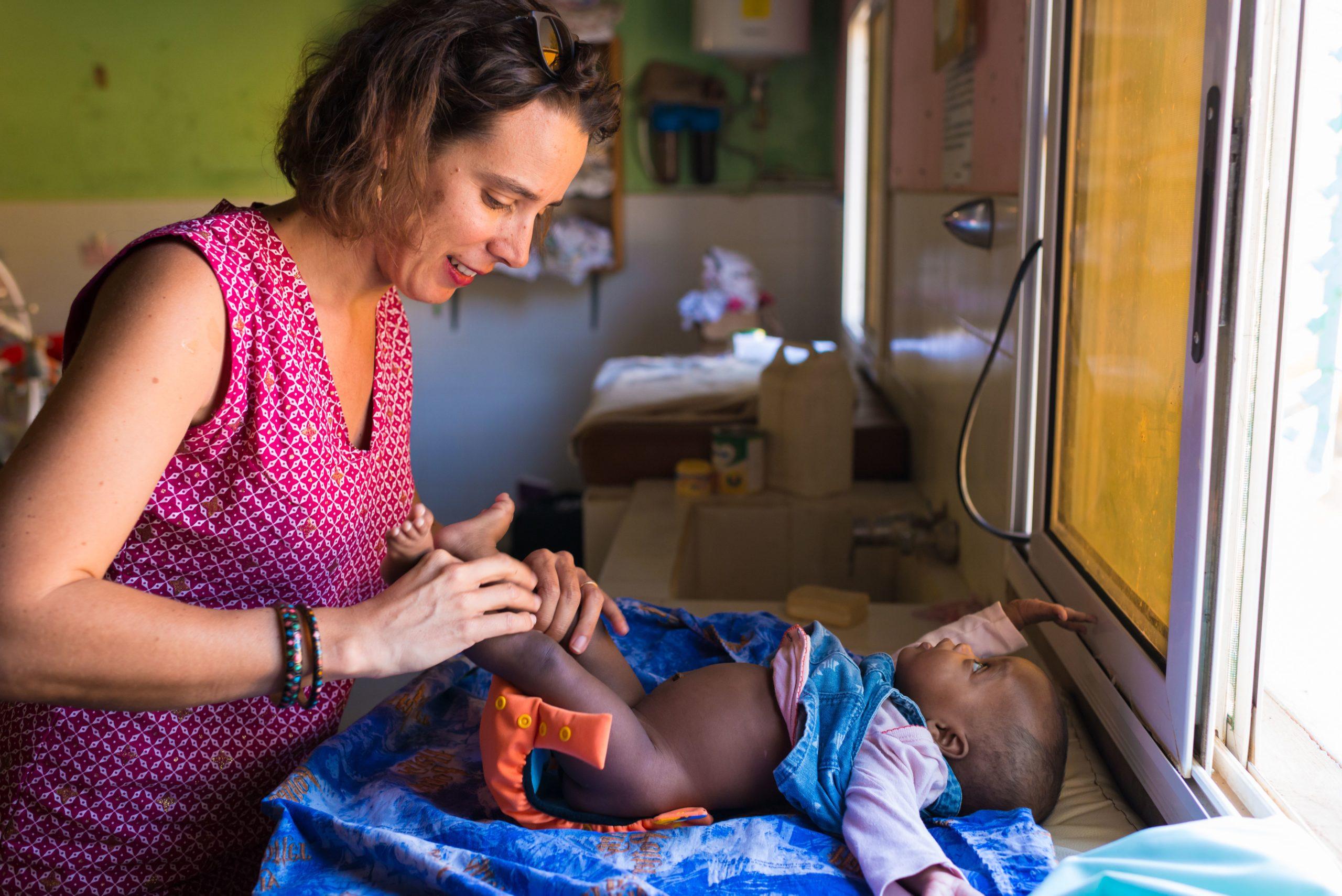 Une femme est en train d'installer une couche lavable toute-en-deux ApiAfrique Orange à un petit garçon