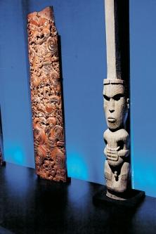 À gauche : Epa (panneaux), entre 1800 et 1900, d'une tribu inconnue, en bois de totara et coquille d'abalone. À droite : Poupou (poteau de soutien à figure masculine) pour mémorial, 1850, sculpté par Iwikau Te Heuheu T?kino III, tribu Ngati Tuwharetoa, en bois de totara.