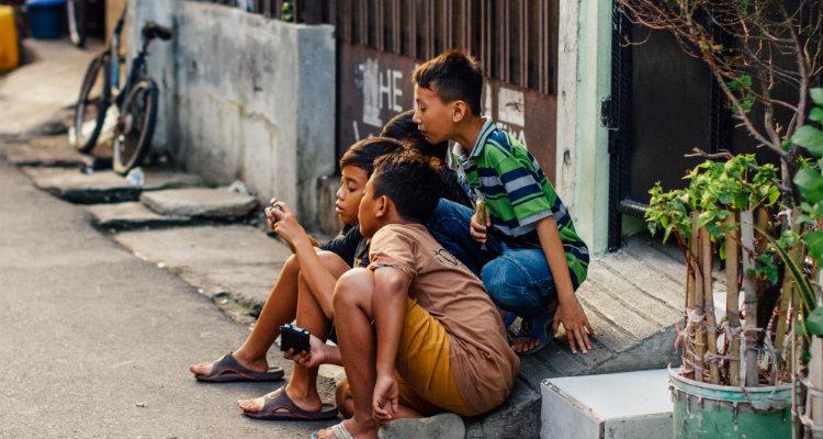Enfants se partageant un téléphone mobile
