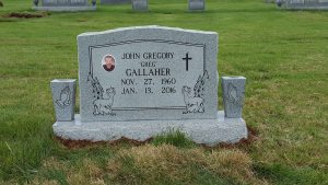 Tombstone with custom art, photo, and vases.