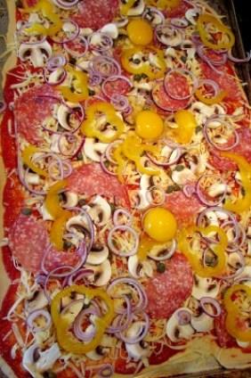 belegde pizza voor hij in de oven gaat