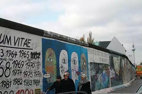 De nombreux immigrés se sont installés dans les quartiers de l'ancien Berlin Est, où l'immobiliser est plus abordable qu'à l'ouest. Leur intégration en ex-RDA, hermétiquement fermée à l'immigration pendant la période communiste et où régnait une grande méfiance vis-à-vis des étrangers, ne s'est pas faite sans difficultés. L'image de ces deux femmes voilées turques passant devant le mur évoque aussi la barrière de séparation d'Israël avec les Palestiniens. Le mur est recouvert de dizaines de tags et d'une fresque faisant le parallèle avec l'ouvrage érigé entre Jérusalem et Abou Dis, de messages de paix appelant à faire tomber les barrières entre les hommes et pour la liberté.