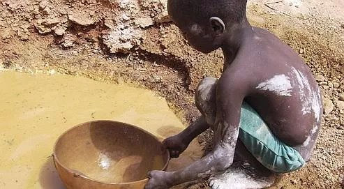 Un enfant extrait de l'or, dans une mine de Djikouloumba en Guinée, en avril 2008. La Guinée possède les premières réserves mondiales de bauxite mais aussi d'importants gisements de fer, d'or et de diamants.