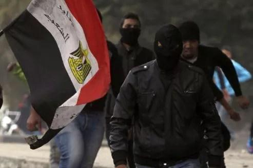 Des membres des Black Blocs paradent avec un drapeau égyptien lors d'affrontements avec la police près de la place Tahrir, lundi au Caire.