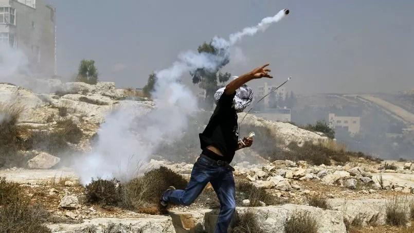 Un Palestinien renvoie un lacrymogène à des soldats israéliens, à Rafah, le 2 août.