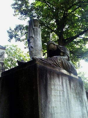 <Photo of a figure on top of a grave at Pere Lachaise cemetery in Paris, France. >