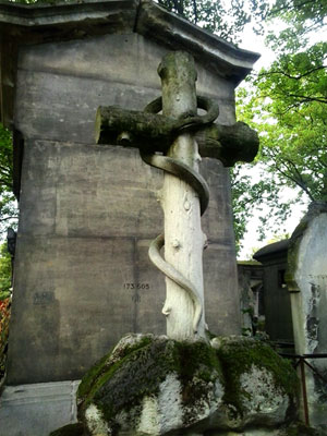 <Photo of a snake and cross grave at Pere Lachaise cemetery in Paris, France. >