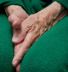 Old woman's hands with deep wrinkles and protruding veins tucked between her legs. She is wearing a bright green sports suit.