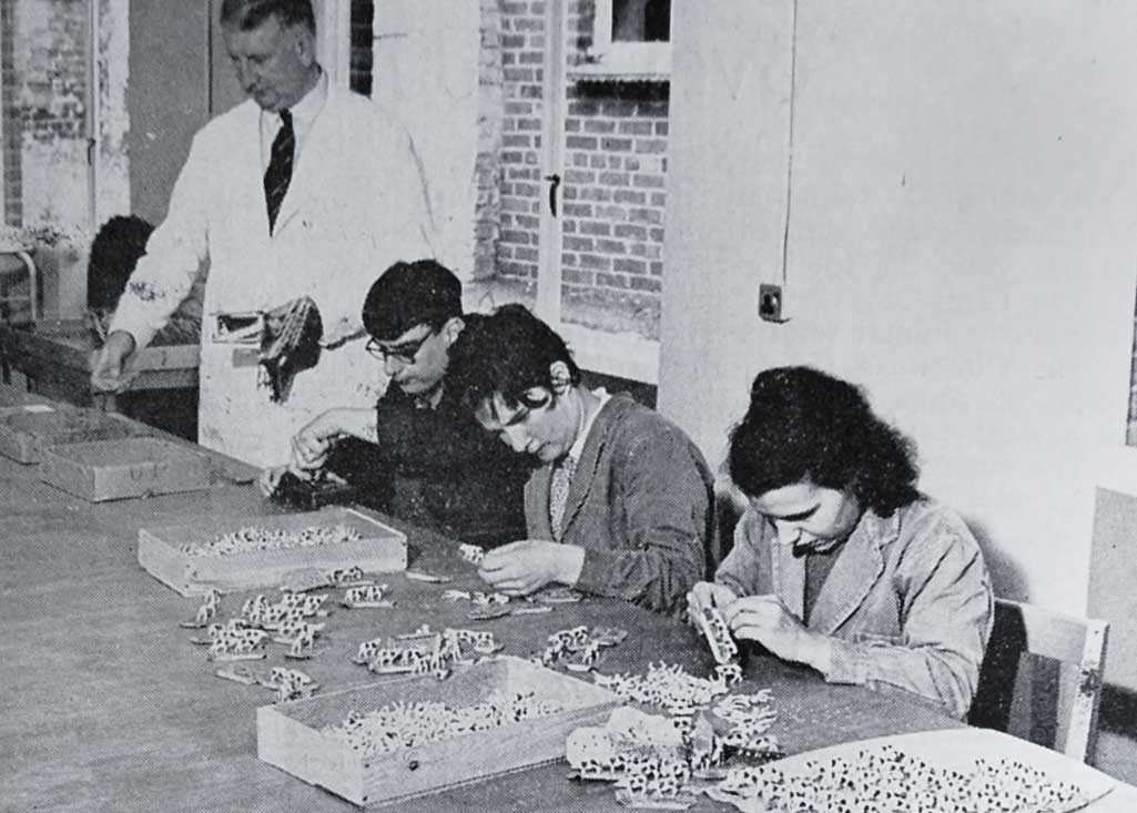 Mr H. McKelvie, The Works Manager, at the head of an assembly line in the production of toy sets, by Richard Lewis, Joan Hubbard and Ann Rogers, a contract undertaken for Mettoys Ltd.