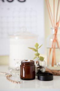 Brown jar of cream, green plant on white surface; image by Maddi Bazzocco, via Unsplash.com.