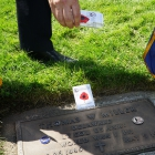 100th Anniversary Observance Committee Chairman and Past National Commander David Rehbein   scatters poppy seeds for remembrance on the grave of American Legion founder Thomas W. Miller. Photo by Holly K. Soria/The American Legion