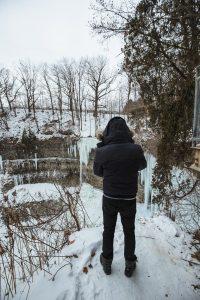 adrian-in-black-jacket-in-front-of-frozen-tew-falls-hamilton-ontario-2018