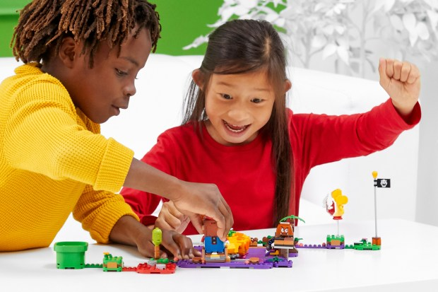 Image of two children playing with a LEGO Super Mario course