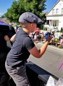 "A young ""newsie"" throws candy from the Lehi Free Press truck in the miniature float parade. 