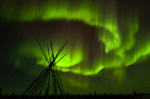Huge green Northern Light, aurora borealis, behind and above the frame of a teepee and boreal forest on the bottom of the picture