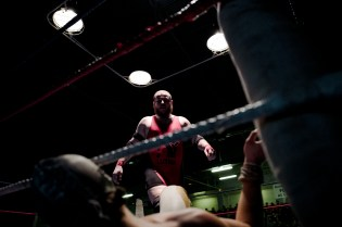 Wrestler Ace Angel, bottom, lays on the matt as rival wrestler PV Red looks on just before catching him at the wrestling charity gala in Ivry Sur Seine, south of Paris, Saturday, Feb. 24, 2018.