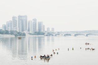 Taedong River / The skyline of new buildings in the Changjon district of Pyongyang that were built by Kim Jong Un. In the front we see people cleaning the river from seaweed