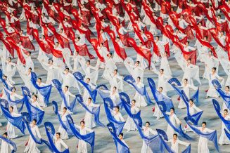 At the Rungrado May Day Stadium (The biggest stadium in the world holding 150 000 seats and 120 000 performers), thousands and thousands of local performers work to produce an immense display of gymnastics, imagery and colour to set out the key political legacies and messages of North Korea