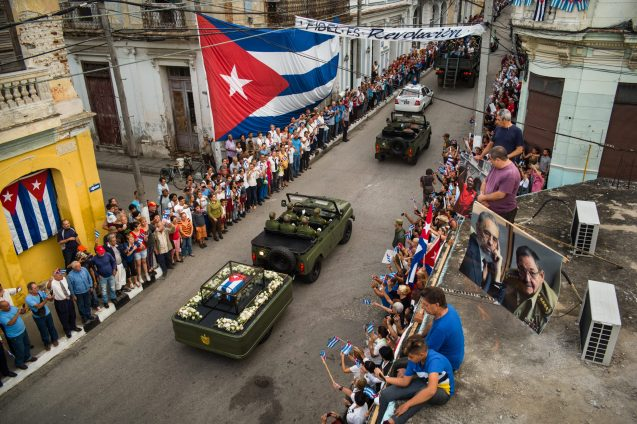"The casket carrying Fidel Castro's ashes moves along the procession route in Santa Clara, Cuba 1 December 2016. Many Cubans, standing everywhere, pay homage to their ""Comandante"", waving national flags. The former President of Cuba died of natural causes on 25 November 2016. After two days of commemoration in Havana the funeral convoy traveled along a 900 km route to Santiago de Cuba, tracing in reverse the route of the ""Freedom Caravan"" of January 1959, in which Castro and his rebels took power after winning the revolution. His ashes were entombed in Santiago de Cuba on 4 December 2016, and hundreds of thousands of Cubans commemorated the event. I was on the rooftop of an old building when the convoy passed."