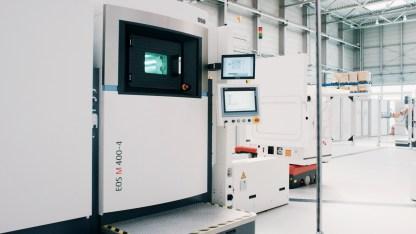 Das auf der EOS M 400-4 additiv gefertigte Bauteil wird in einem Container mittels fahrerlosem Transportfahrzeug zur nächsten Station befördert (Quelle: EOS).
