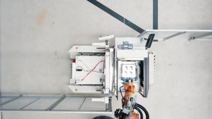 Ein Roboter entnimmt die additiv gefertigten Bauteile, die sich noch auf der Bauplattform befinden (Quelle: EOS).