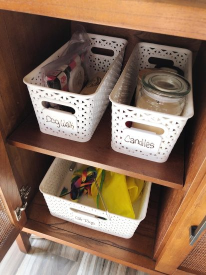 organize living room cabinet with plastic baskets