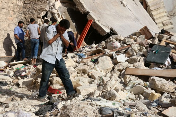 A Syrian man reacts as rescuers look for victims under the rubble of a collapsed building following a reported air strike on the rebel-held neighbourhood of Sakhur in the northern city of Aleppo on July 19, 2016. Civilians in rebel-held parts of Syria's Aleppo expressed fears on July 18, 2016 of a lengthy government siege, as food supplies dwindled after regime troops seized the only road into the city's east. The government advance, which has been backed by a Russian air offensive, is seen as a major setback for opposition forces in Syria's second city. / AFP PHOTO / THAER MOHAMMED