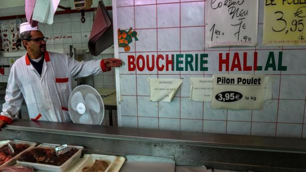 "A butcher points an inscription which translates as ""Halal butchery"" in his butchery on August 2, 2016 in Lille, northern France. The question of the financing of the Muslim Faith, now considered to be insufficiently transparent, continues to shake the political class, after a new opinion pirce by French Prime Minister Manuel Valls in the French newspaper Liberation, where the Prime Minister does not rule out ""a form of public funding."" ""A Funding by the faithuls throw a traditional manner or a newer one like the halal or the crowdfunding is quite possible and it is more consistent with the vision of our country"" he pleaded. / AFP PHOTO / PHILIPPE HUGUEN"
