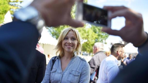 """A supporter takes a picture of Florence Portelli (C), candidate for the presidency of France's right-wing Les Republicains (LR - The Republicans) party, at the party's """"summer days"""" conference in La Baule, western France, on September 2, 2017. / AFP PHOTO / LOIC VENANCE"""