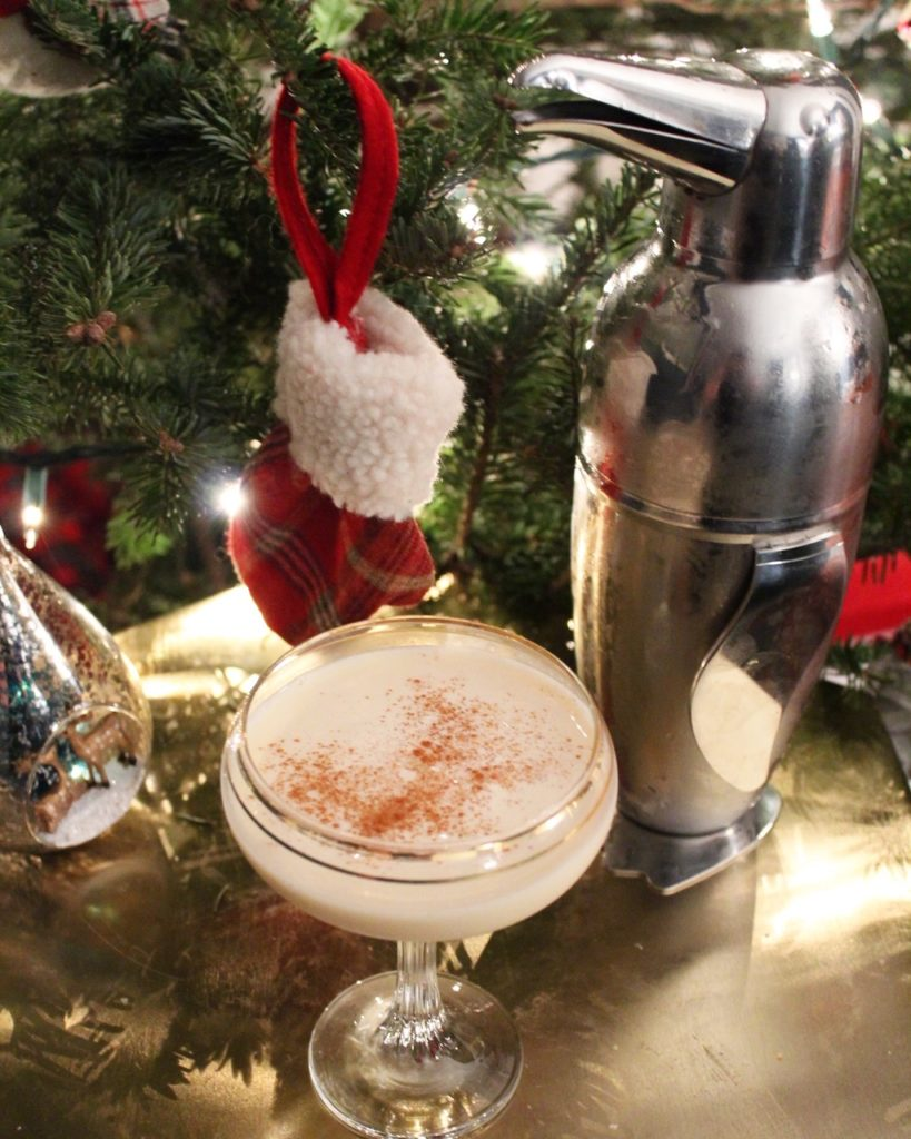 Eggnog cocktail next to Christmas tree