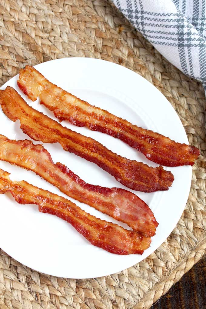 Slices of crispy bacon on a white plate.