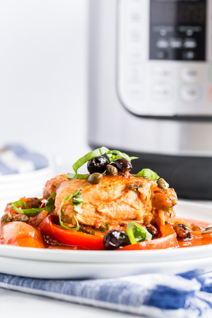 A plate of chicken cacciatore next to an instant pot.