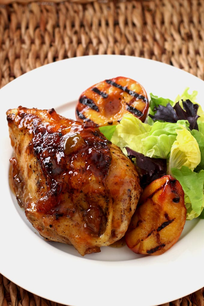 Peach glazed grilled chicken breast on a white plate