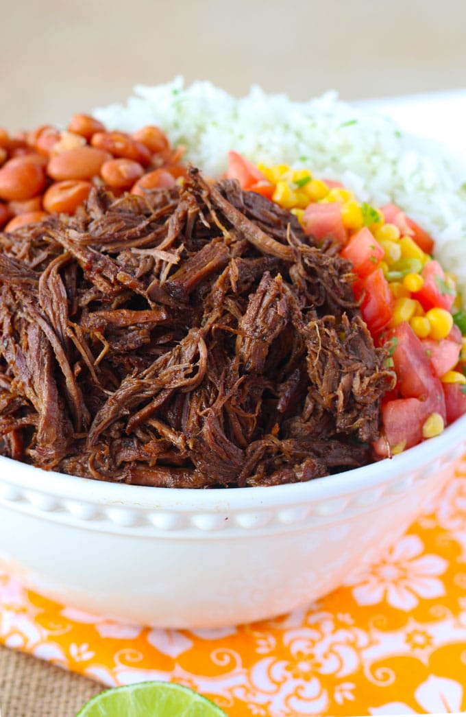 Close up of a bowl of barbacoa beef with rice, beans and corn salsa