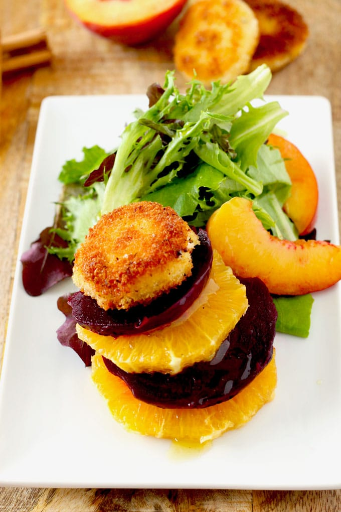 View of the roasted beet salad on a white plate. A stack of thin round slices of orange and beets topped with a crispy goat cheese coin.