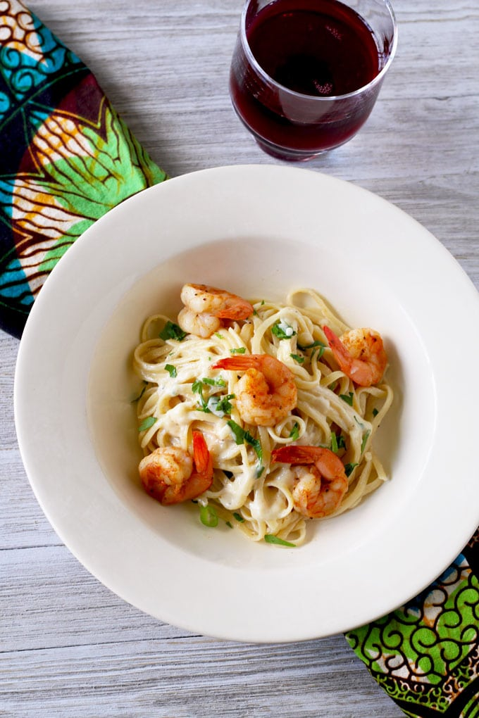 Over view of a plate with Cajun shrimp Alfredo pasta next to a glass of wine