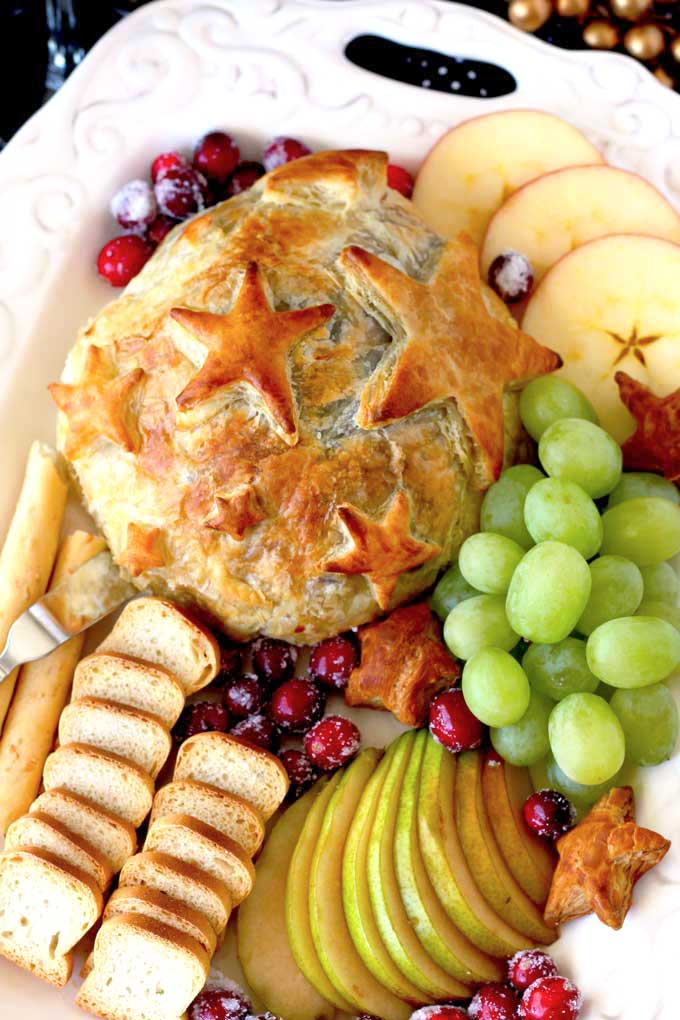 Overhead view of Baked Brie with Cranberries served with fruit and crackers.