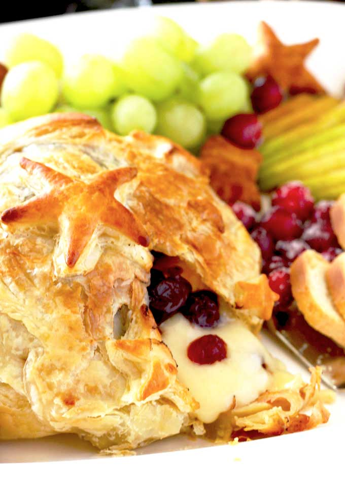 Close up of melted Baked Brie served with fruit and crackers