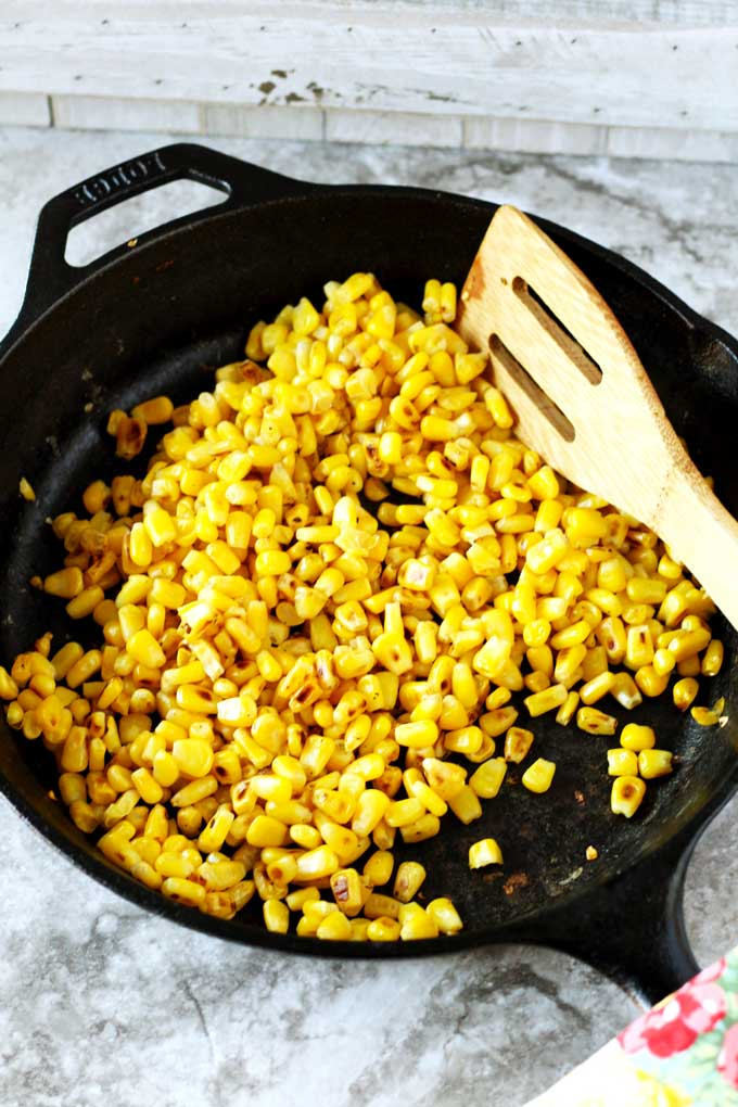 Corn kernels roasting in a cast iron skillet.