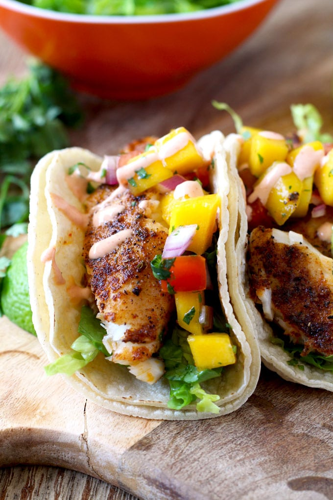 Close up of Blackened Fish Tacos with Mango Salsa and Sriracha Aioli on a wooden surface