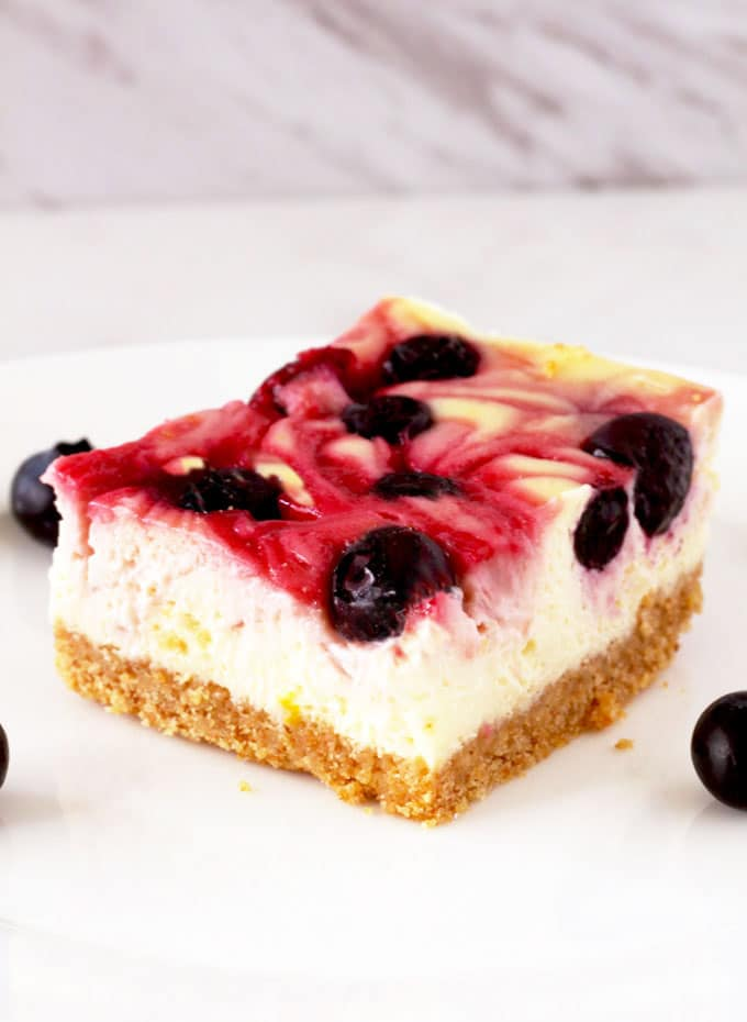 Creamy, smooth and delicious. These Mixed Berry Swirl Cheesecake Bars are studded with fresh blueberries and swirled with raspberries. Quick and easy to make, they are the perfect dessert to make for your next party or get together!