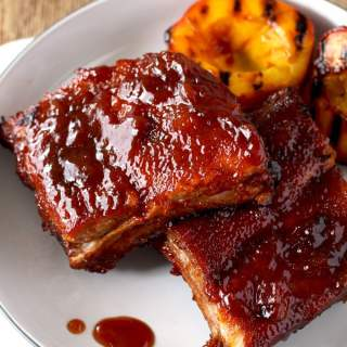 These Mouthwatering Bourbon and Peach BBQ ribs are seasoned with a simple spice rub mix and cooked in the oven until fall-off-the-bone tender. Smothered in a lip-smacking Bourbon and Peach BBQ sauce, these ribs are easy, delicious and foolproof!